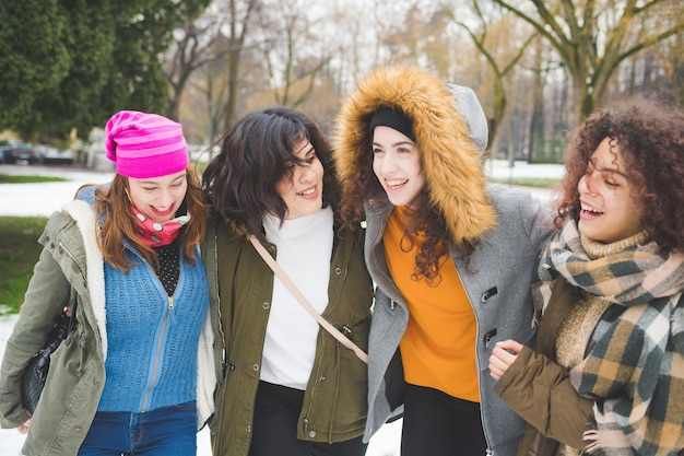 Quatro, mulheres jovens, multi-étnico, abraçando, campo neve, rir Foto Premium