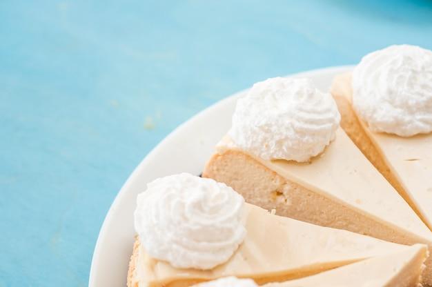 Quatro pedaços de bolo de queijo em um fundo azul Foto Premium