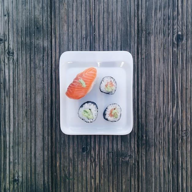 Quatro pedaços de sushi no prato pequeno Foto gratuita