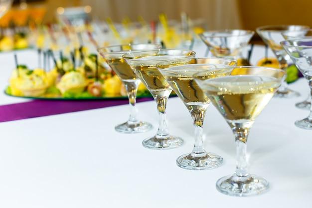 Quatro taças de champanhe na mesa do banquete Foto Premium