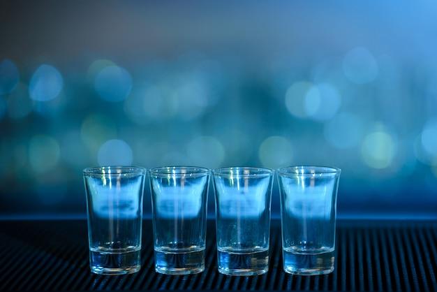 Quatro tiros de tequila em uma barra de mesa de madeira. Foto Premium