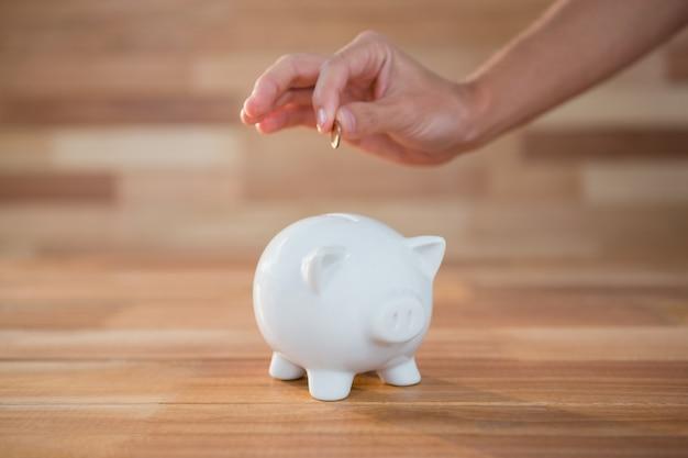 Que introduz a moeda mão no banco piggy Foto gratuita