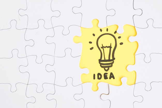 Quebra-cabeça amarelo idéia destacam-se das peças brancas Foto gratuita