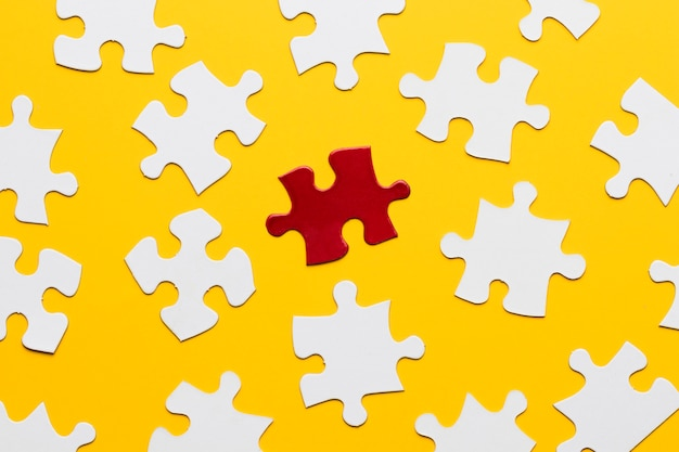 Quebra-cabeça brilhante vermelho entre branco contra pano de fundo amarelo Foto gratuita