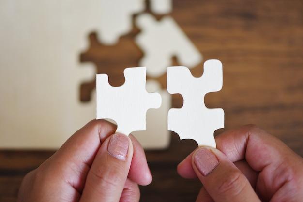 Quebra-cabeça com mão de mulher, conectando a peça de quebra-cabeça Foto Premium