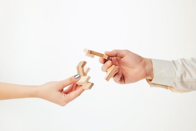 Quebra-cabeça de madeira de brinquedo nas mãos isolado no branco Foto gratuita