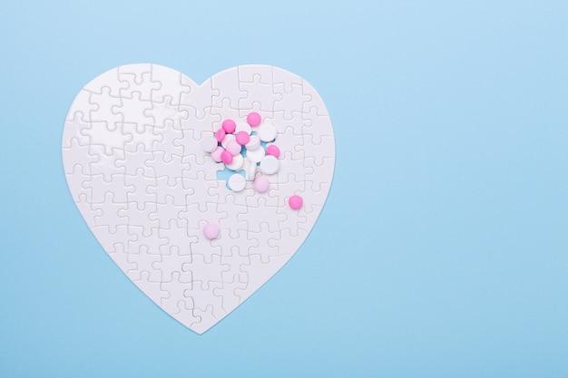 Quebra-cabeça em forma de coração branco e rosa comprimidos em azul Foto Premium