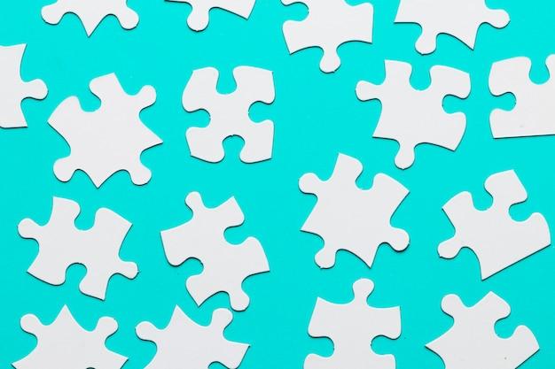 Quebra-cabeças de papelão branco peças no pano de fundo turquesa Foto gratuita