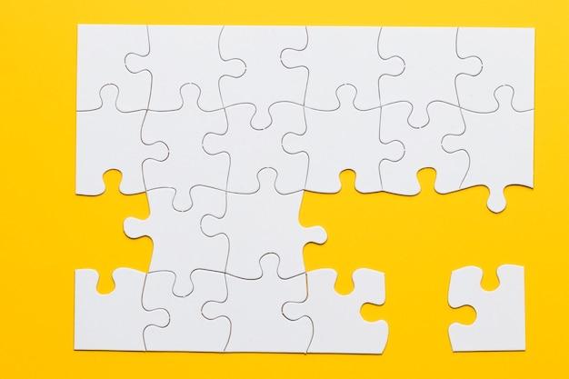 Quebra-cabeças de papelão branco sobre fundo amarelo Foto gratuita