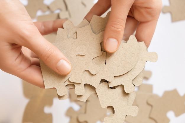 Quebra-cabeças de papelão nas mãos femininas, close-up. Foto gratuita