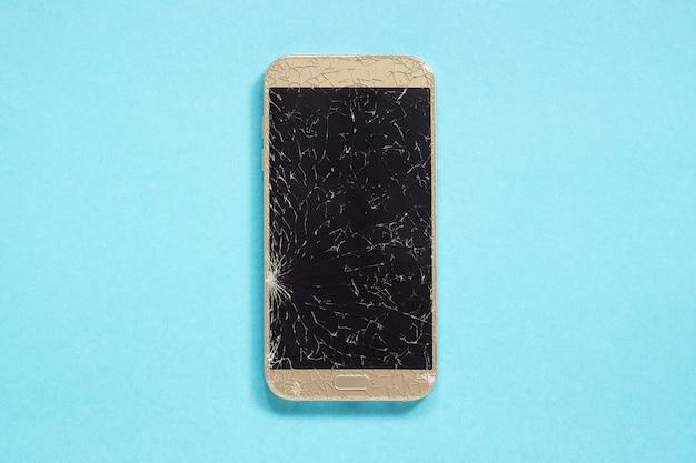 Quebrado rachaduras celular no fundo azul Foto Premium