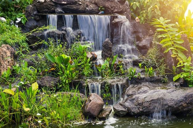 Queda pequena artificial da água na decoração do espaço verde da casa do jardim do parque. Foto Premium