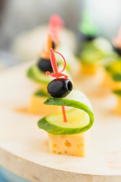 Queijo, azeitona e pepino no espeto de plástico na placa Foto gratuita
