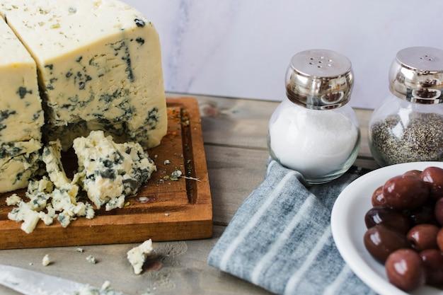 Queijo azul com azeitonas; sal e pimenta preta shaker com guardanapo na mesa de madeira Foto gratuita