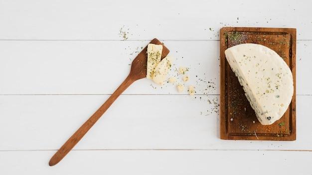 Queijo azul e espátula na tábua de madeira sobre a mesa branca Foto gratuita