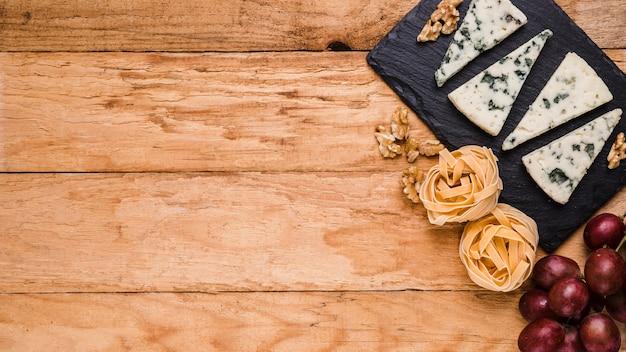 Queijo azul em pedra ardósia; noz; uvas e macarrão cru sobre a mesa com espaço para texto Foto gratuita
