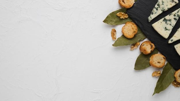 Queijo azul; fatia de pão; noz e folhas de louro com fundo de espaço de cópia Foto gratuita