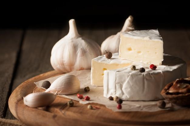 Queijo camembert e brie em de madeira com tomates, alface e alho. comida italiana. lacticínios. Foto Premium