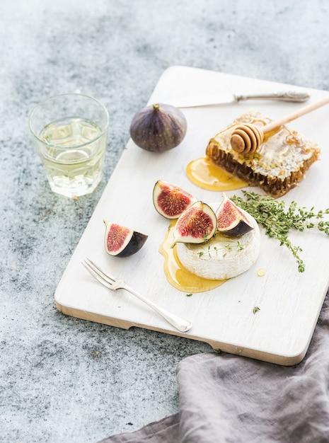 Queijo camembert ou brie com figos frescos, favo de mel e copo de vinho branco na mesa de servir sobre cinza rústico grunge Foto Premium