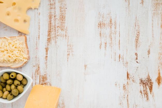Queijo cheddar com azeitonas verdes na mesa de madeira branca Foto gratuita