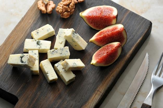 Queijo com mofo azul dorblu, algumas fatias de figos e nozes são servidos em uma tábua de madeira. há talheres nas proximidades. Foto Premium