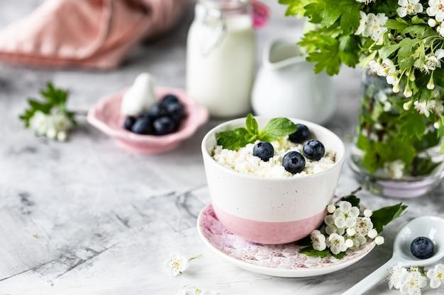 Queijo cottage café da manhã com mirtilos, creme, leite em uma mesa branca e um ramo de flores. Foto Premium