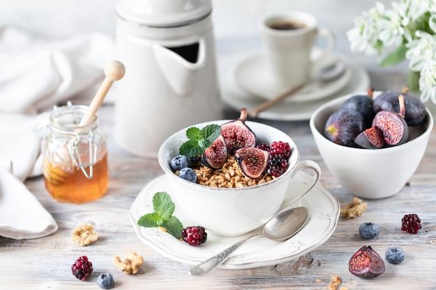 Queijo cottage com figos, frutas, mel. xícara de café e cafeteira. café da manhã. mesa de madeira. Foto Premium