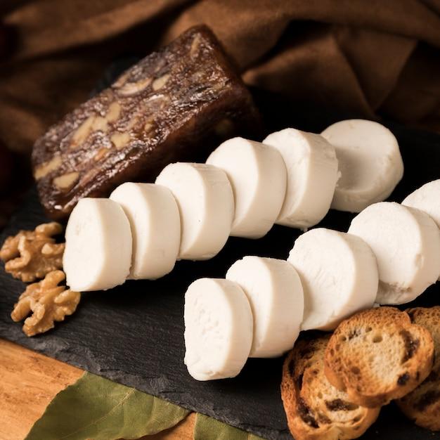 Queijo de cabra orgânica, queijo castanho, noz e pão com folhas de louro em pedra ardósia Foto gratuita