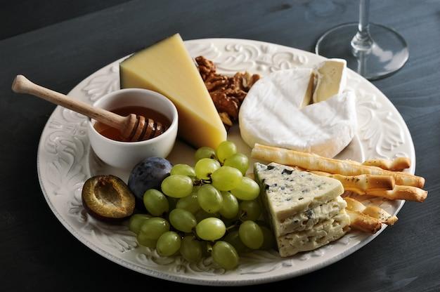 Queijo de sobremesa, palitos de pão, mel, nozes e uvas Foto Premium