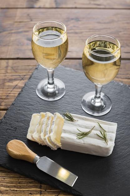 Queijo e copos de vinho branco de alta vista Foto gratuita