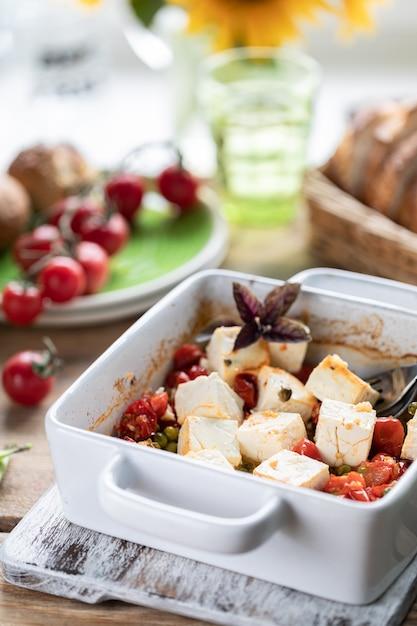 Queijo feta assado com tomate cereja com manjericão e azeite. cozinha nacional grega. Foto Premium