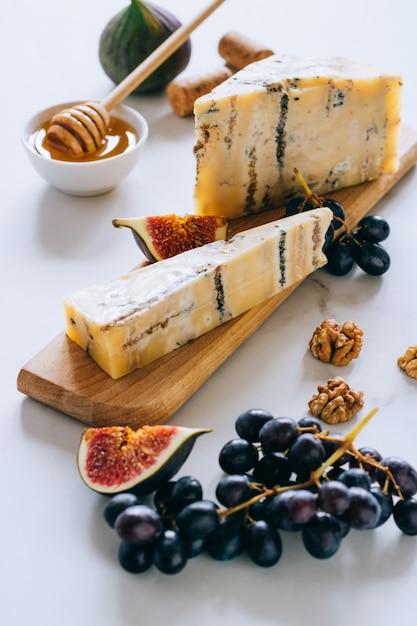 Queijo inglês velho de stilton. queijo azul, figos e uvas em uma tábua de cozinha em mármore Foto Premium