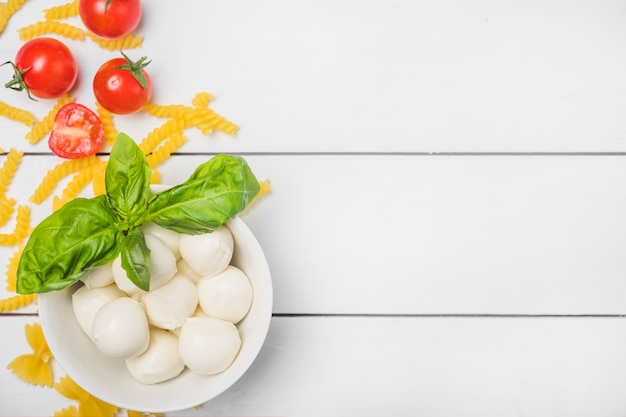 Queijo mussarela italiano com folhas de manjericão; tomate e macarrão fusilli na prancha de madeira branca Foto gratuita