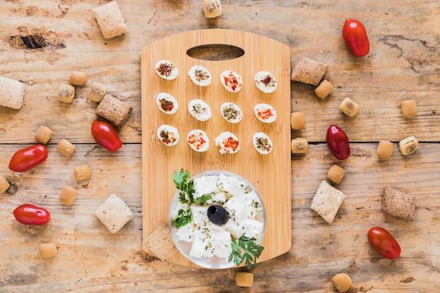 Queijo na tábua com tomate e pastelaria na mesa Foto gratuita