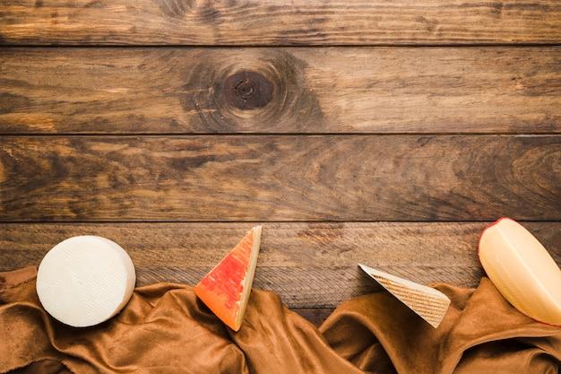 Queijo orgânico organizado em uma linha com marrom têxtil na mesa de madeira Foto gratuita