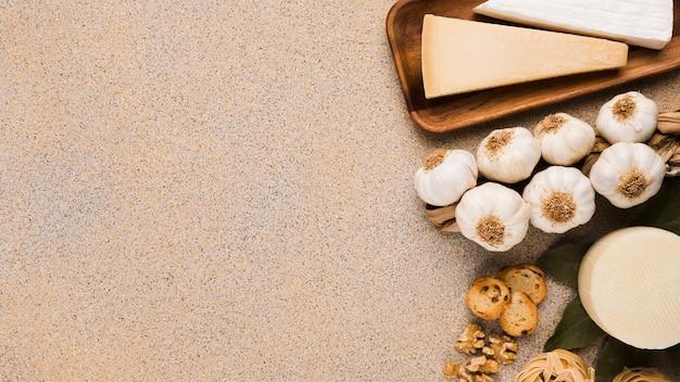 Queijo parmesão; queijo de manchego espanhol de bulbos de alho sobre a superfície texturizada com espaço para texto Foto gratuita