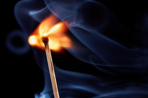 Queima de fósforo com fumaça em fundo preto Foto Premium