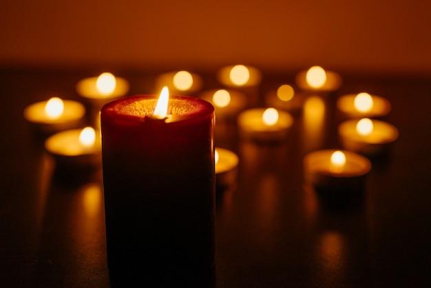 Queima de velas. profundidade superficial de campo. muitas velas acesas à noite. muitas chamas de velas brilhando. Foto Premium