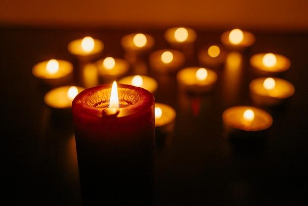 Queima de velas. profundidade superficial de campo. muitas velas de natal acesas à noite. muitas chamas de velas brilhando. Foto Premium