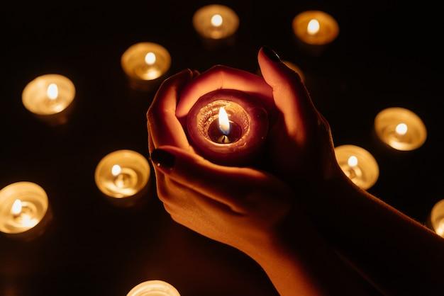 Queima de velas. vela em mãos femininas. muitas velas acesas à noite. muitas chamas de velas brilhando. Foto Premium
