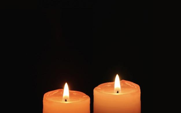 Queimando par de velas laranja em fundo preto Foto Premium