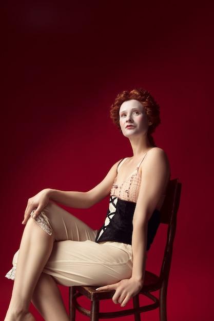 Quem está no controle. jovem ruiva medieval como uma duquesa em espartilho preto e roupa de noite, sentada na cadeira na parede vermelha. conceito de comparação de eras, modernidade e renascimento. Foto gratuita