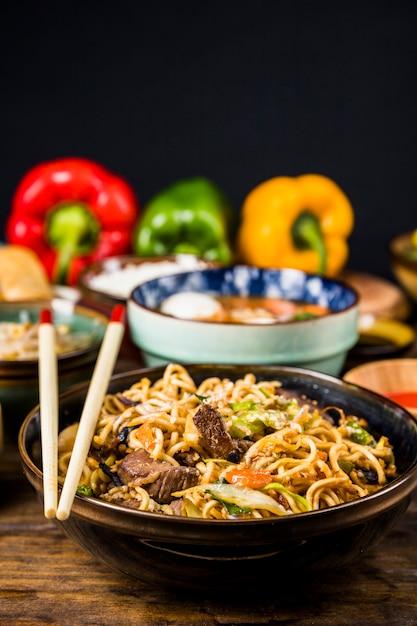 Quente e picante stir frito macarrão instantâneo com carne e vegetais em tigela de cerâmica Foto gratuita