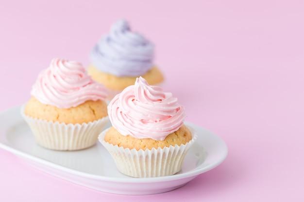 Queque decorado com buttercream cor-de-rosa e violeta no fundo do rosa pastel. Foto Premium