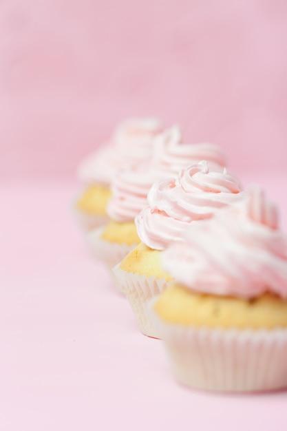 Queque decorado com buttercream cor-de-rosa no fundo do rosa pastel. bolo lindo doce Foto Premium