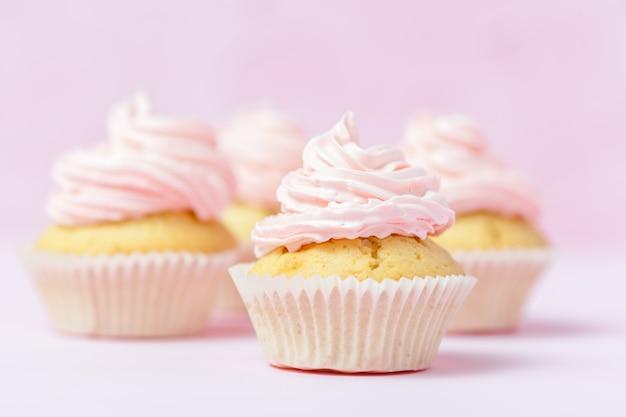 Queque decorado com buttercream cor-de-rosa no fundo do rosa pastel. Foto Premium