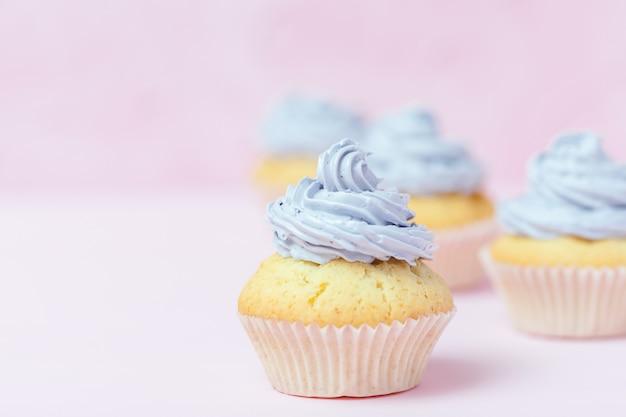 Queque decorado com buttercream violeta no fundo do rosa pastel. Foto Premium