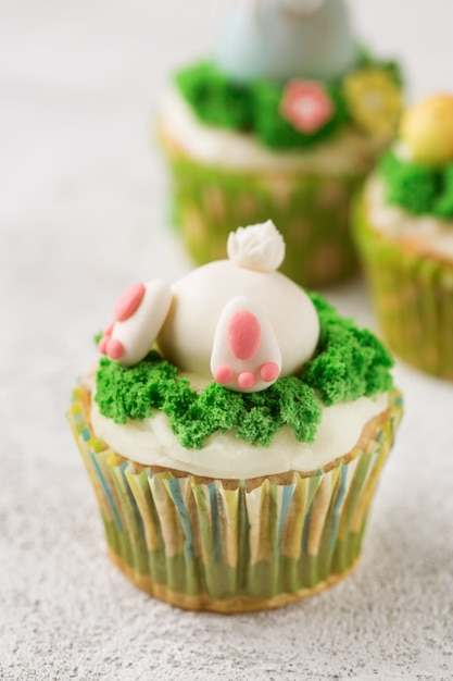 Queques da páscoa com coelho e grama engraçados no fundo branco. conceito de feriado de páscoa Foto Premium