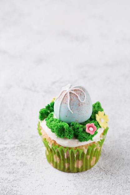 Queques da páscoa com ovos e grama de mástique na tabela. conceito de feriado de páscoa. espaço da cópia Foto Premium