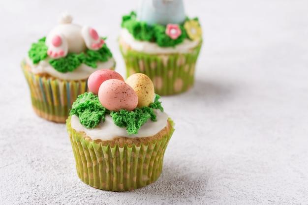 Queques festivos com ovos e grama de mástique no fundo brilhante. conceito de feriado de páscoa. espaço da cópia Foto Premium